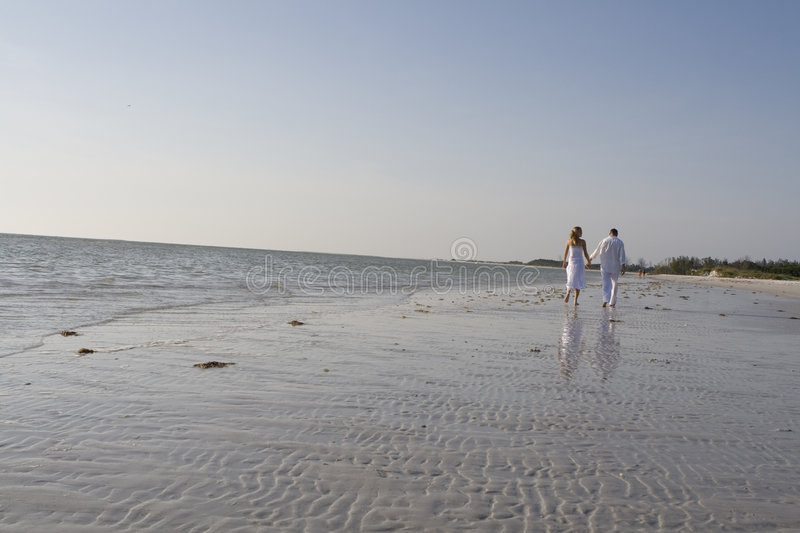 Romantic walk. Man and a woman walking on a beach. Both wearing white clothes stock image