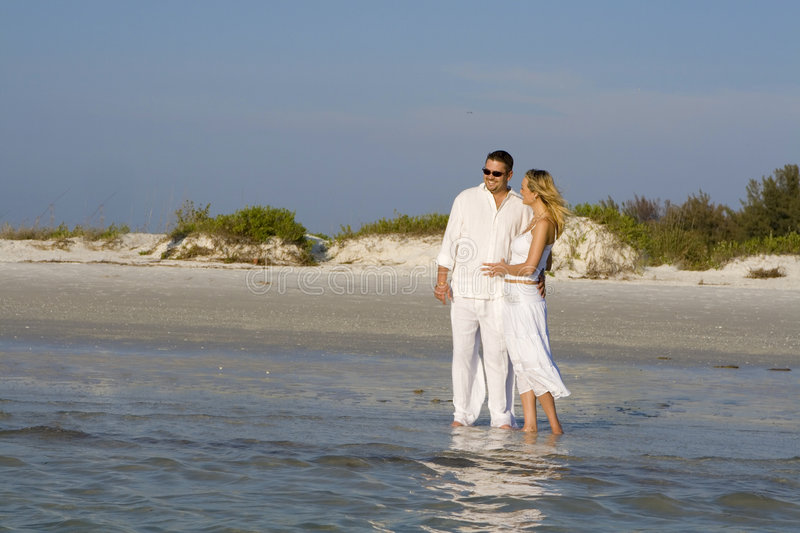 Romantic walk. Man and a woman standing on a beach. Both wearing white clothes royalty free stock photo