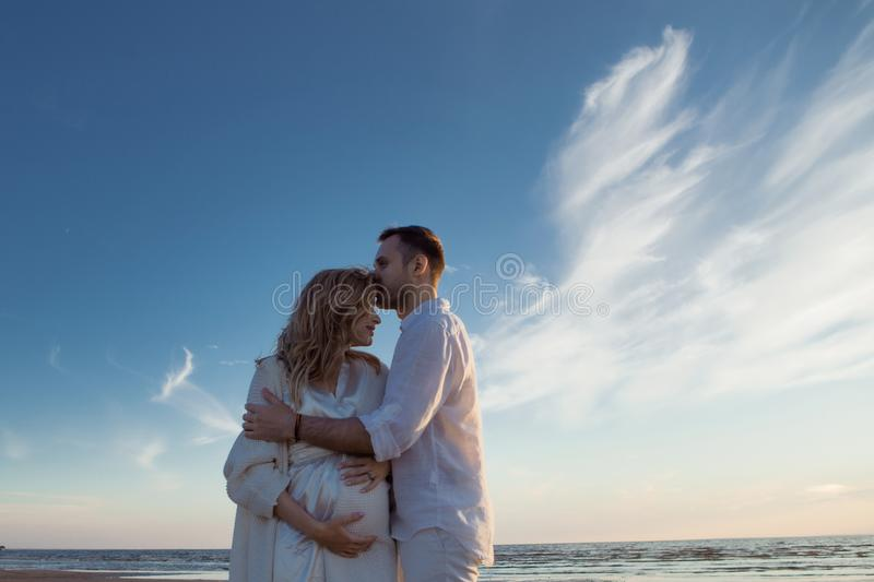 Romantic walk on the beach, waiting for a baby. Happy young couple hugging tummy, spending time by the sea. royalty free stock image