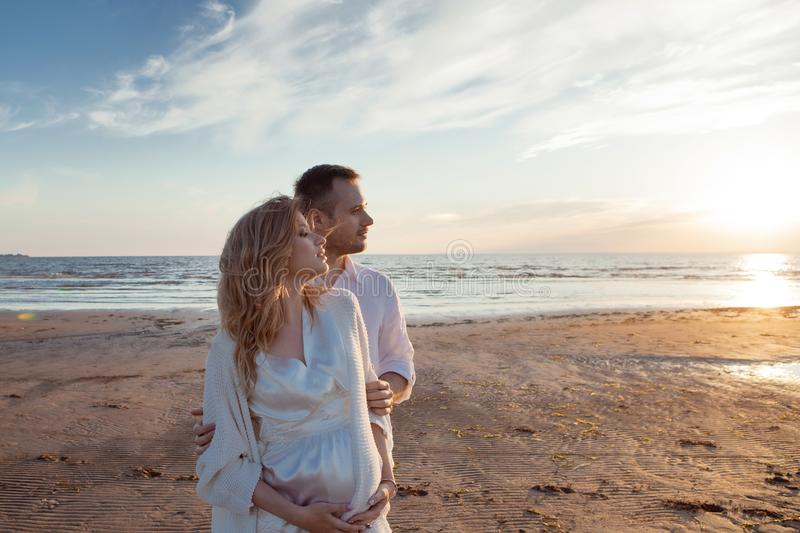 Romantic walk on the beach, waiting for a baby. Happy young couple hugging tummy, spending time by the sea. Romantic walk on the beach, waiting for a baby stock images