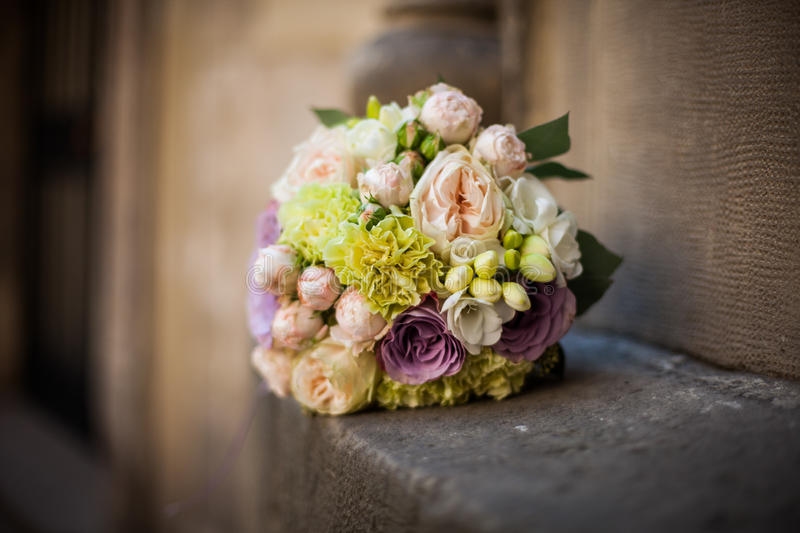 Romantic wedding bouquet, pink, purple and white roses on a stone closeup stock photo