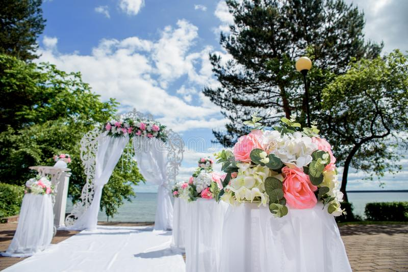 Romantic wedding ceremony on the lawn Sea view. White and pink wedding flowers stock photography