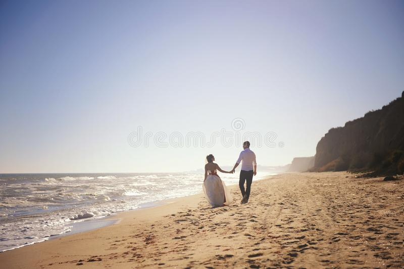 Romantic wedding couple celebrating marriage outdoors on a sea beach royalty free stock image
