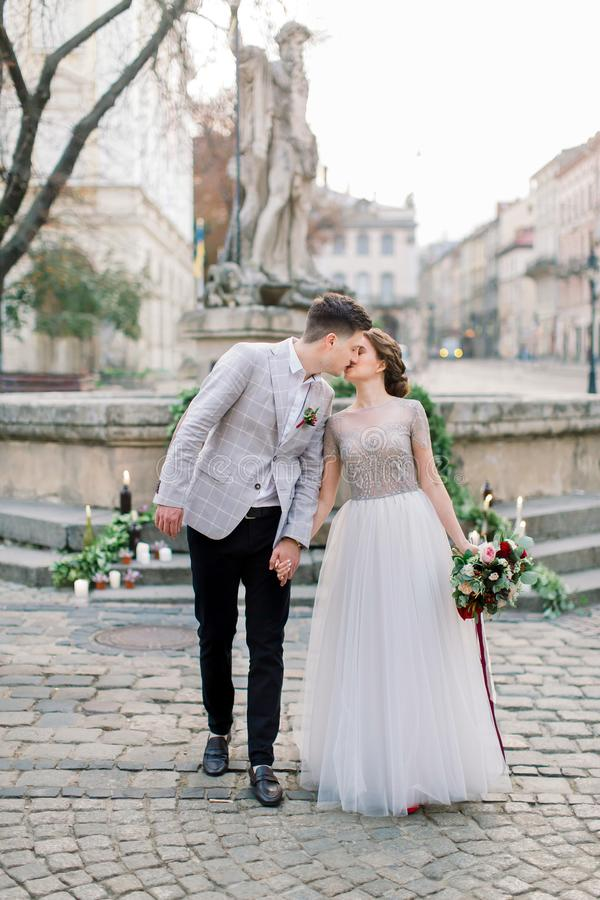 Romantic wedding couple in love, walking and kissing, holding hands. Wedding decor on the stone stairs, monument stock image