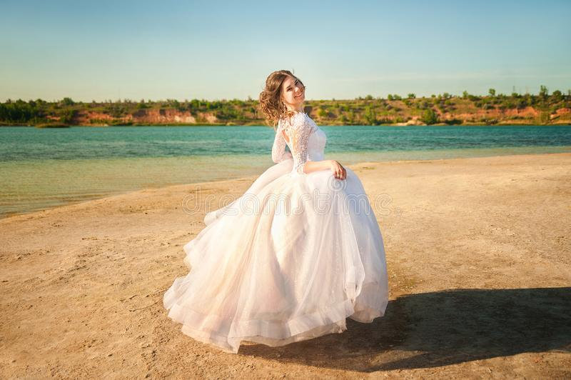 Romantic wedding couple on the shore. The bride runs along the shore against the backdrop of a lake or sea close-up and copy space royalty free stock images