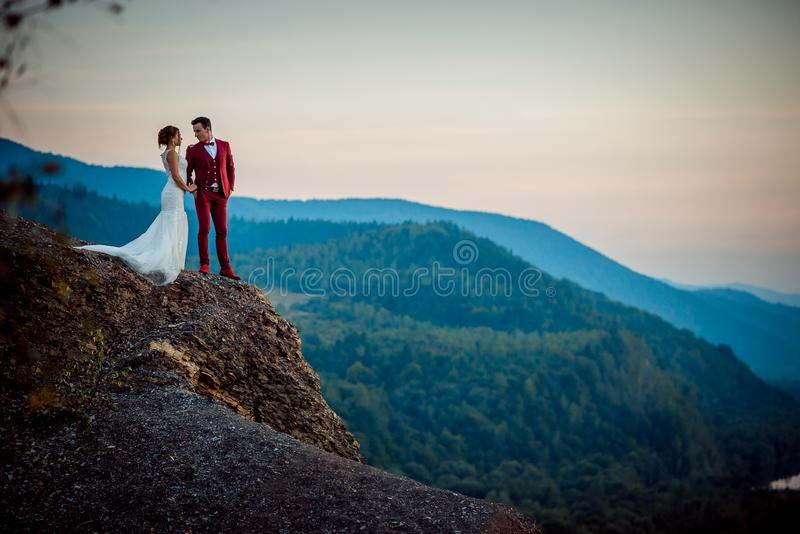 Romantic wedding shot. Charming newlyweds are holding hands on the edge of the mountains. Beautiful landscape during the stock image