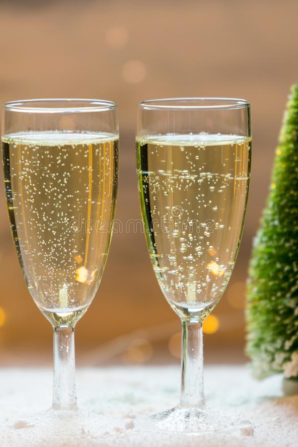 Romantic, white and golden winter background with two glasses of champagne stock image