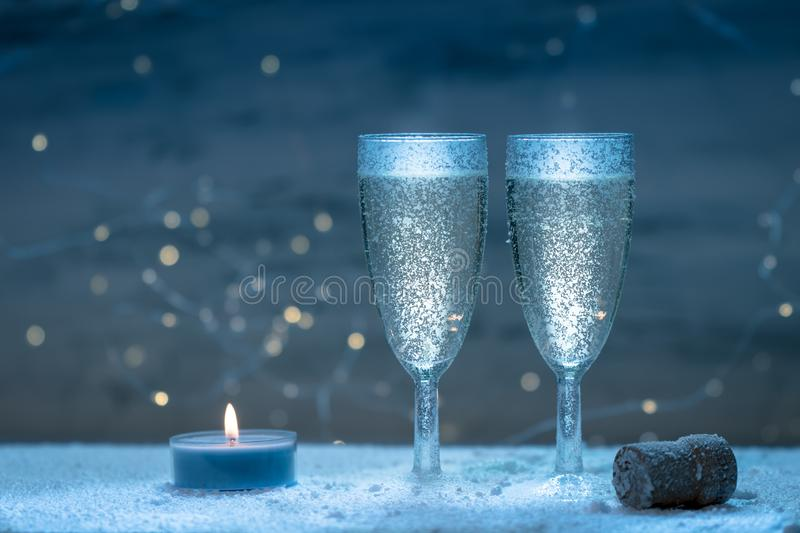 Romantic, white and golden winter background with two glasses of champagne royalty free stock image