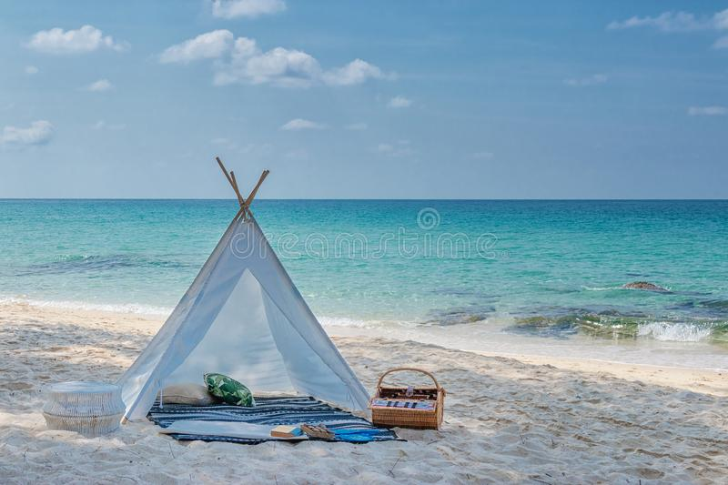 Romantic white picnic tent on white sand beach with crystal clear water and blue sky at background stock photography