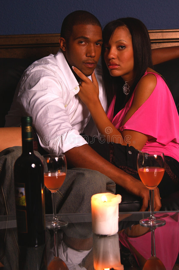 Romantic Wine. African American couple share a romantic candlelit glass of wine