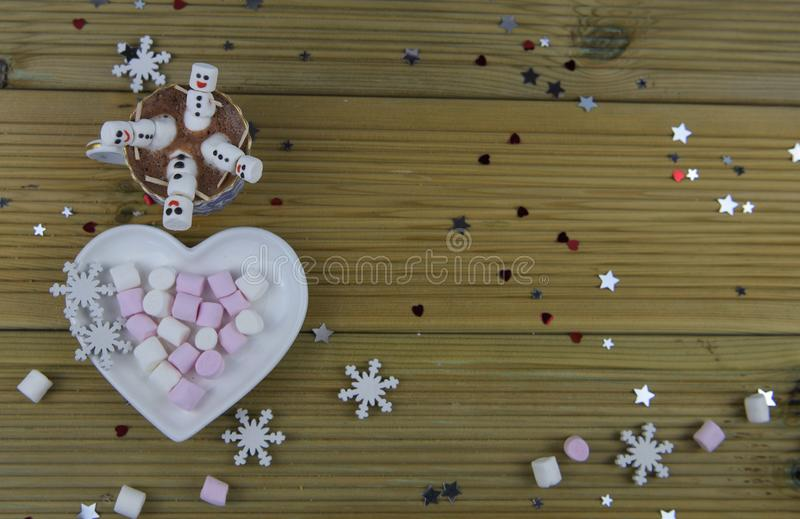 Romantic winter season photography food and drink image with hot chocolate cup and mini marshmallows shaped as happy snowman stock photos
