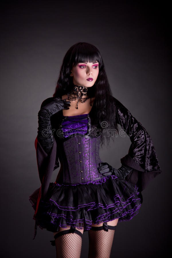 Romantic witch in purple and black gothic Halloween outfit royalty free stock photography