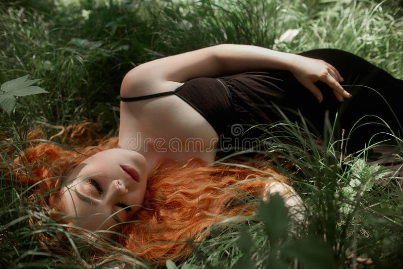 Romantic woman with red hair lying in the grass in the woods. A girl in a light black dress sleeps and dreams in a magical forest. royalty free stock photography