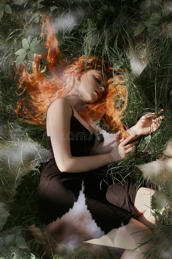Romantic woman with red hair lying in the grass in the woods. A girl in a light black dress sleeps and dreams in a magical forest. Romantic woman with red hair stock photography