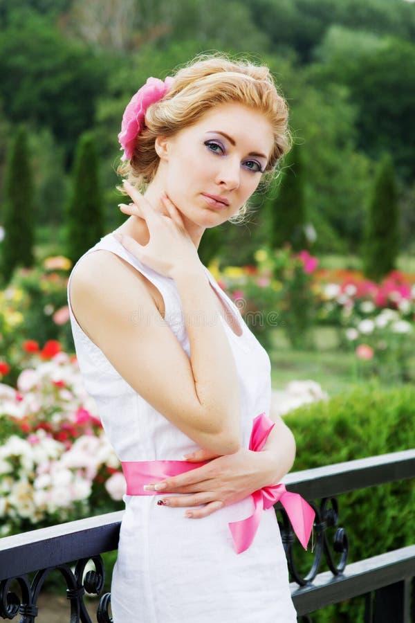 Romantic woman among rose garden royalty free stock image