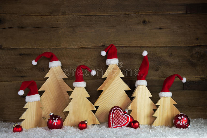 Romantic wooden christmas background with red santa hats and cra. Fted trees with snow royalty free stock photo