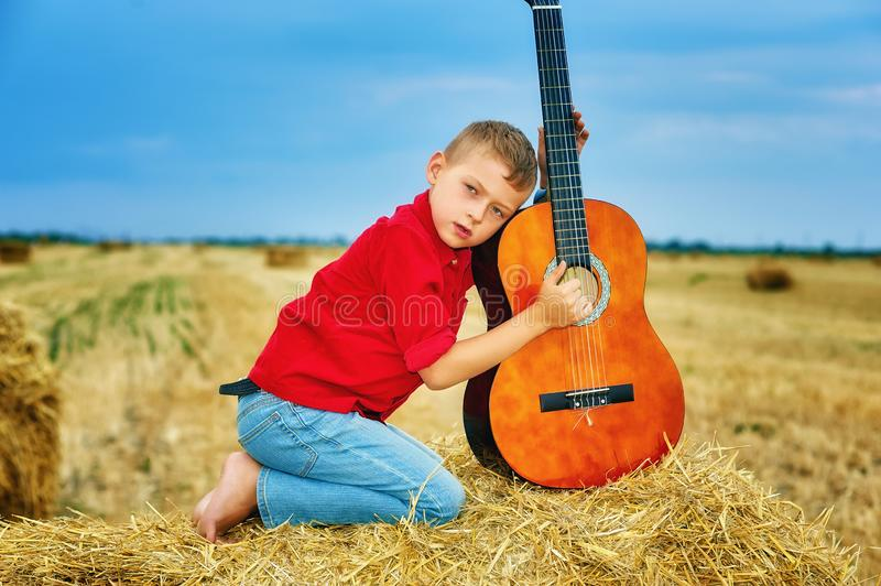 Romantic young boy with guitar in the field royalty free stock image