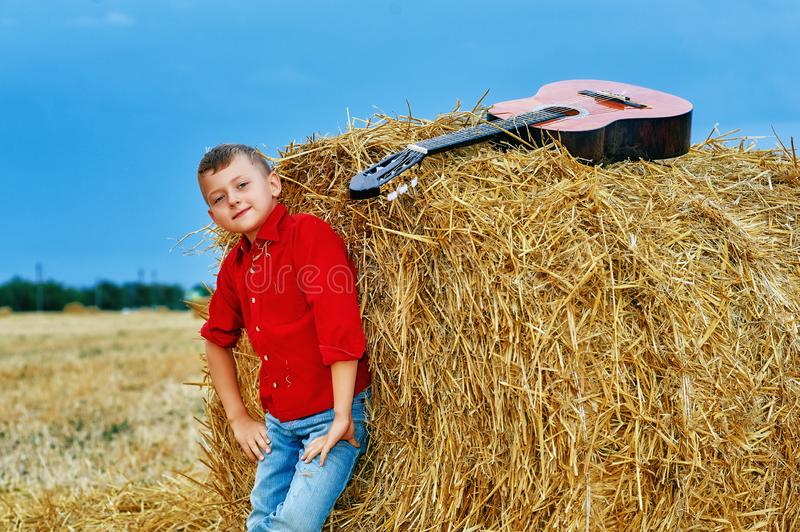Romantic young boy with guitar in the field stock photography