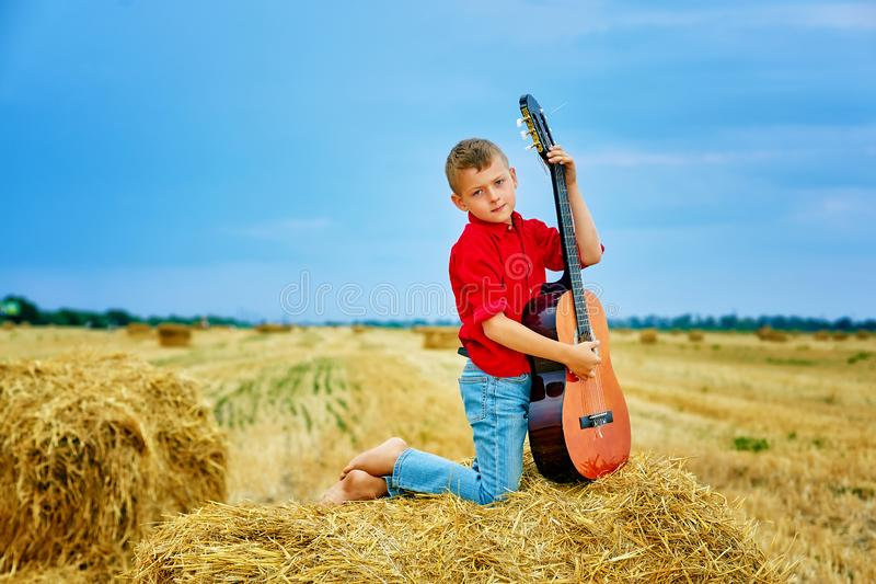 Romantic young boy with guitar in the field stock image