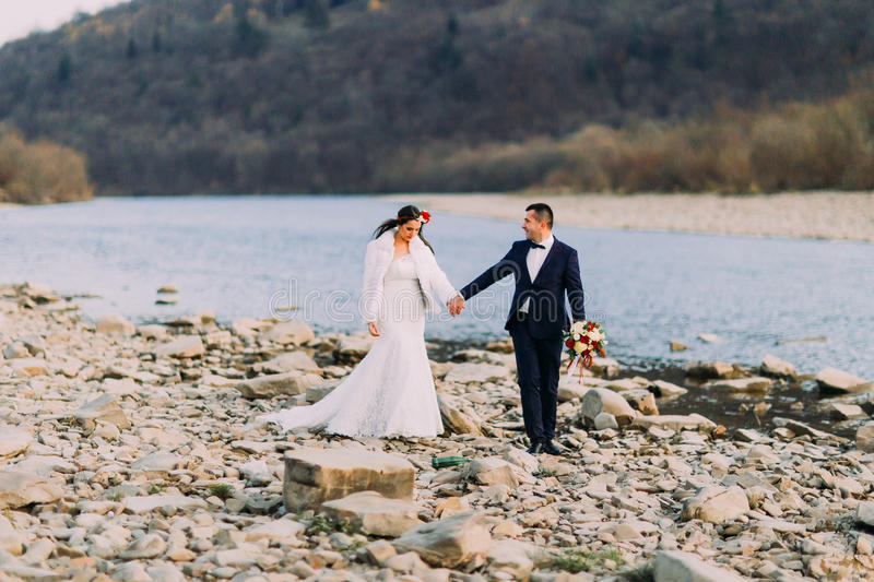 Romantic young bridal couple holding their hands on pebble riverside with forest hills as background royalty free stock photo