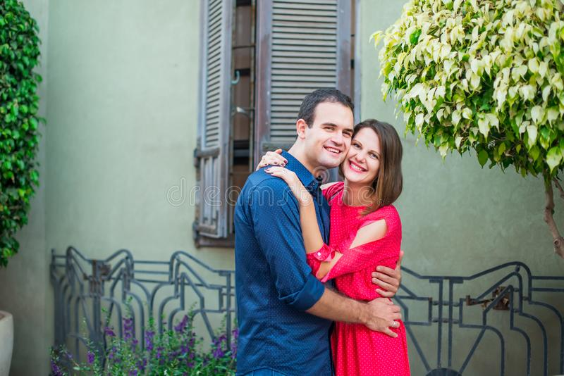 Romantic young couple in bright red and blue clothes embracing and laughing looking to camera on the mediterranean style street. L stock images