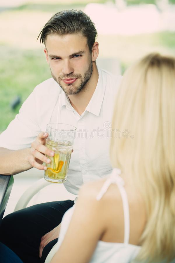 Romantic young couple drink at table in restaurant. Or cafe outdoor, flirting, enjoying, relaxing conversation royalty free stock image