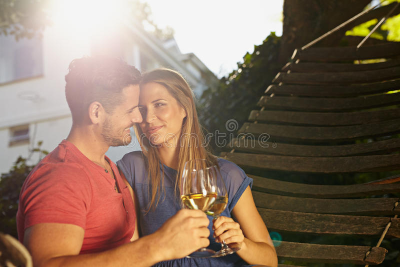 Romantic young couple in hammock toasting wine. Romantic young couple sitting on garden hammock toasting wine. Loving young couple celebrating with a glass of royalty free stock image