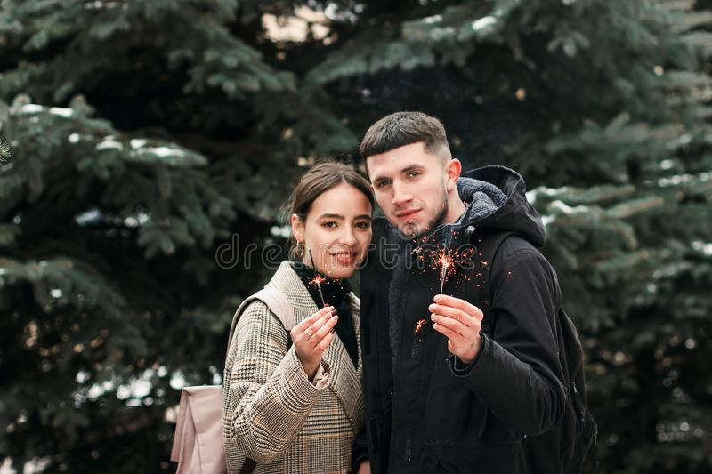 Romantic young couple is having fun outdoors in winter before Christmas with bengal lights stock images