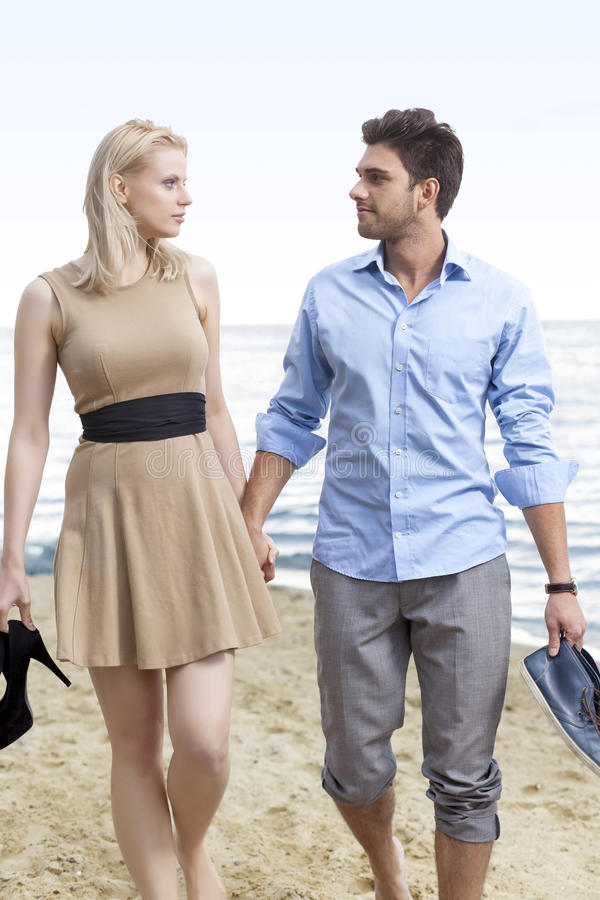 Romantic young couple holding hands and walking on beach royalty free stock photos