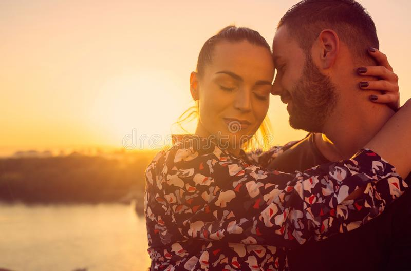 Romantic couple kissing outdoor at the sunset royalty free stock images