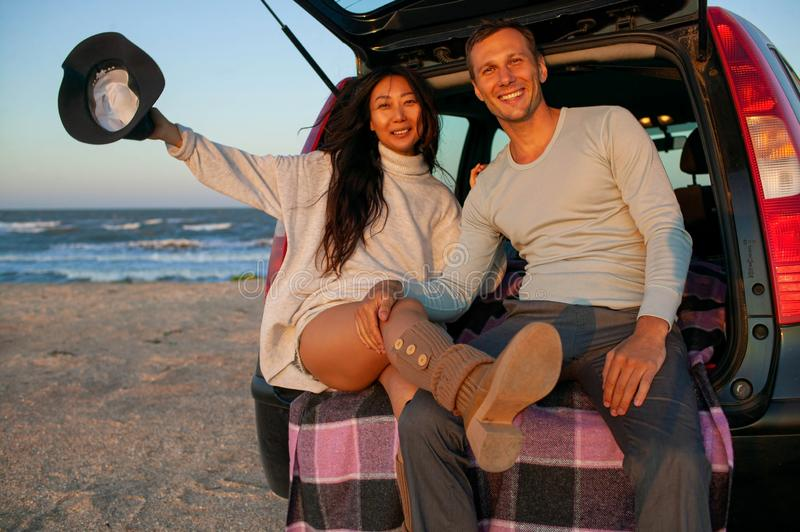 Romantic young couple leaning at car on beach at sunset in autumn. stock photo