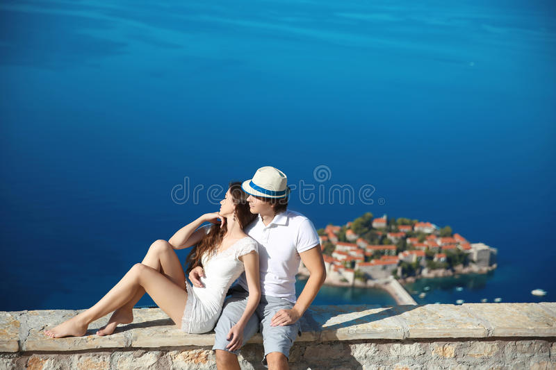 Romantic young couple in love over sea shore above Sveti Stefan island in Budva, Montenegro. Travel. Vacation. Family. Life stock photography