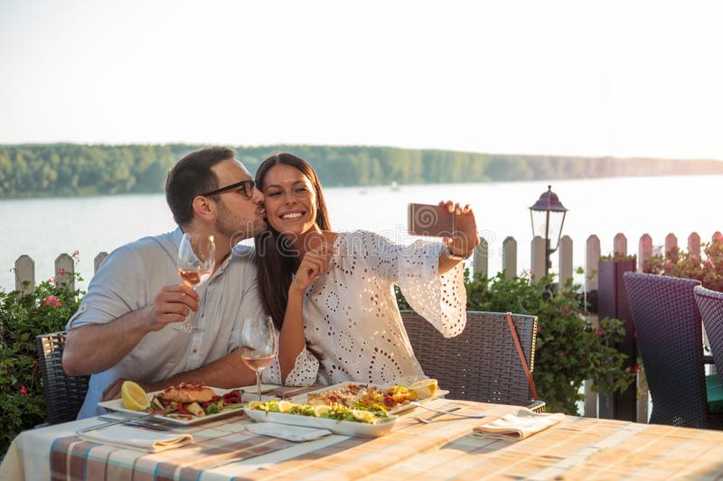 Romantic young couple posing for a selfie, eating dinner in a riverside restaurant. Smiling happy young couple posing for a selfie, eating dinner in a riverside royalty free stock photography