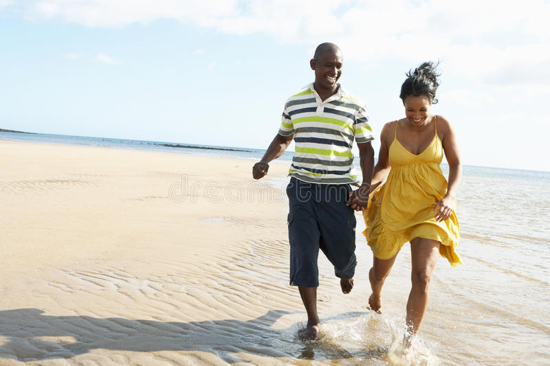 Download Romantic Young Couple Running Along Shoreline Stock Photo - Image: 13673366