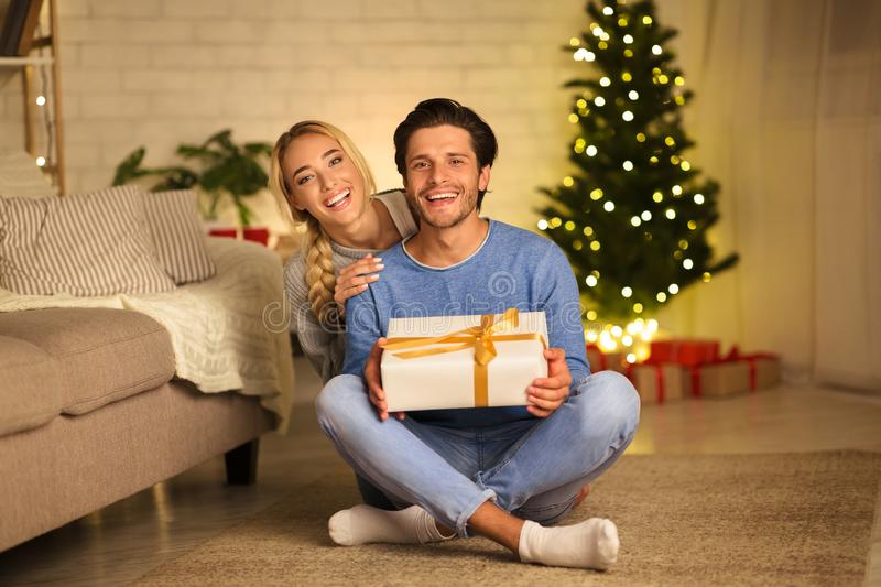 Romantic young couple sitting against Christmas tree royalty free stock photos