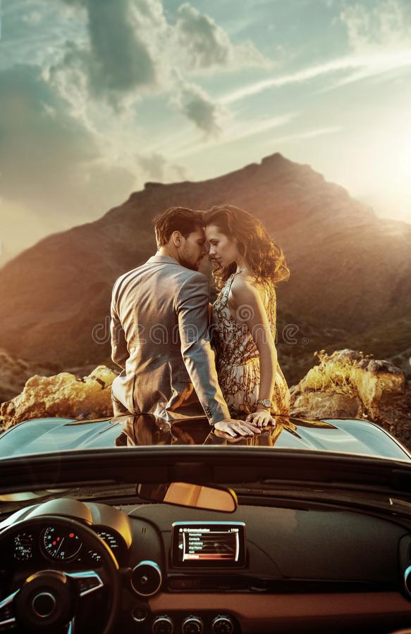 Romantic couple sitting on the bonnet stock photo