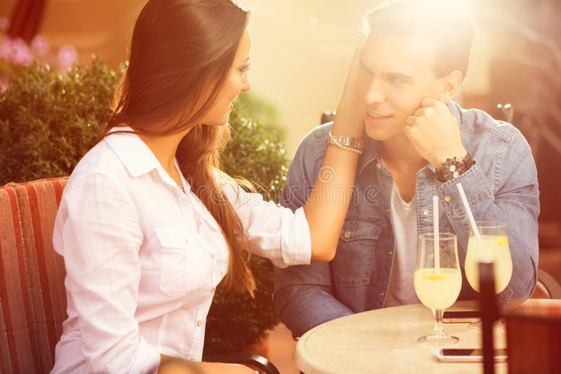 Romantic young couple sitting in a cafe stock photos