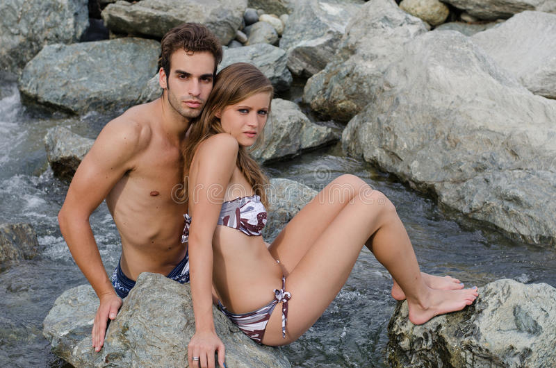 Romantic young couple in swimming suit on rocks stock photography