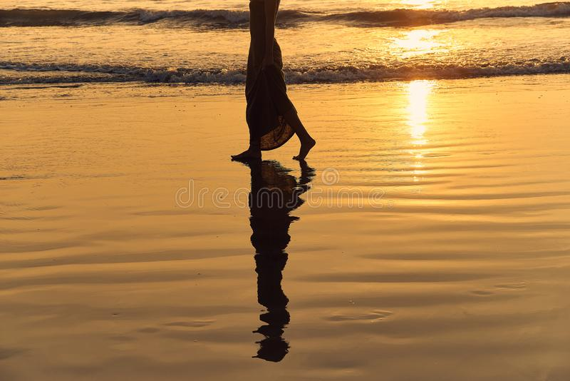 Romantic young girl walks on the beach barefoot in the water. Woman stroll barefoot in the sea at sunset. Beautiful female legs in the ocean. Silhouette of a stock image