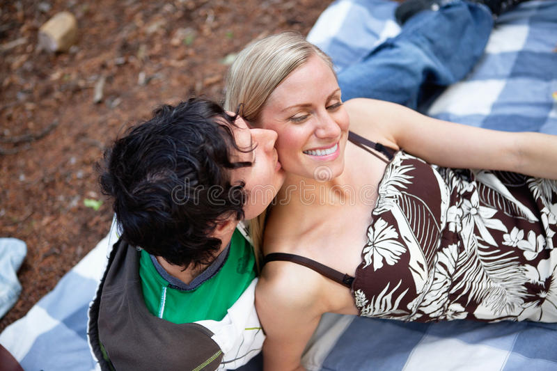 Romantic young guy kissing happy female stock photography