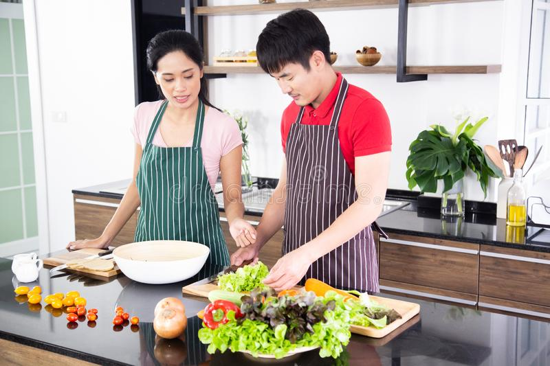 Romantic young lovely couple cooking food in the kitchen royalty free stock images