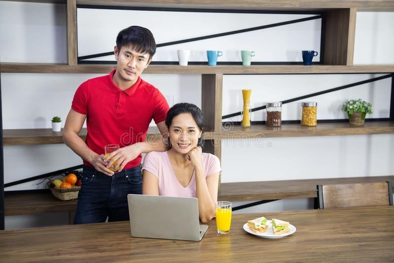 Romantic Young lovely couple drinking orange juice and eat sandwich in the kitchen stock photography