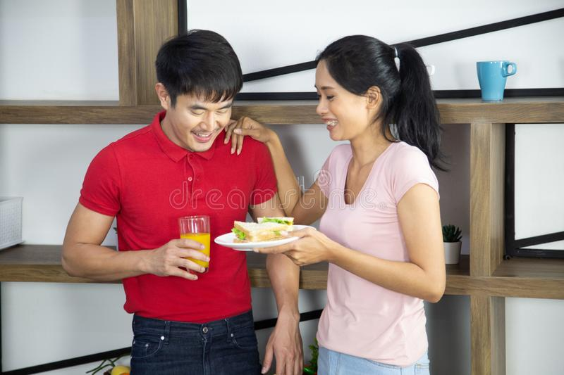 Romantic Young lovely couple show sandwich in the kitchen royalty free stock photos