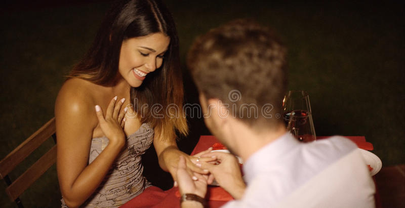 Romantic young man proposing to his love. Romantic young men proposing to his love kneeling on the floor as he places the ring on her finger during a romantic royalty free stock photo