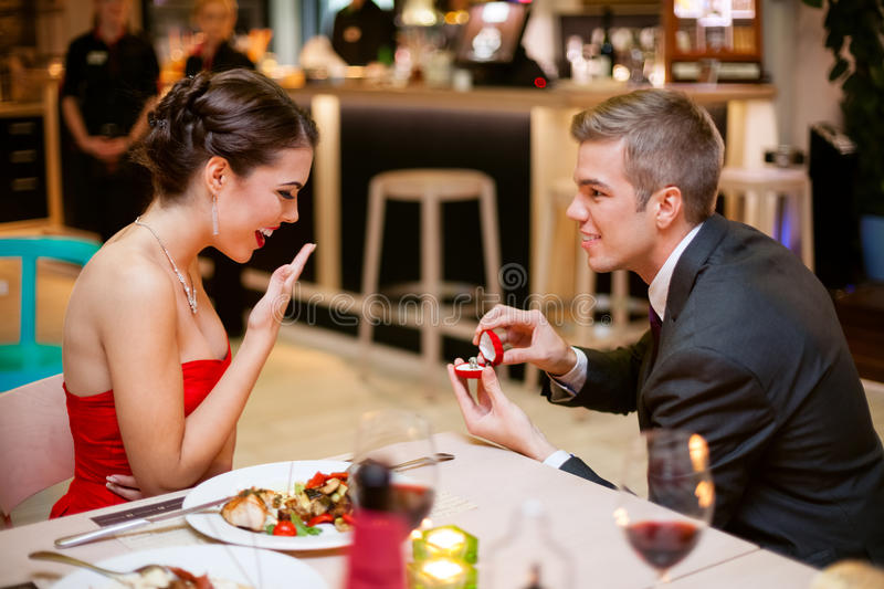 Romantically proposing. Young men romantically proposing to girlfriend and offering engagement ring royalty free stock photo