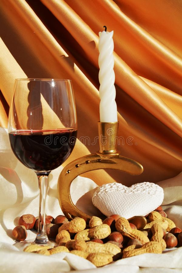 Romanticism and expectation. A mystical candle, a glass of wine and a white shaped heart, on a beautiful golden background, suggesting romanticism and royalty free stock photography