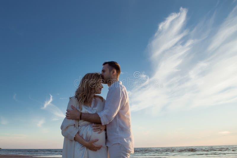 Romantiker går på stranden, att vänta på för att behandla som ett barn Lyckliga unga par som kramar magen som spenderar tid vid h royaltyfri bild