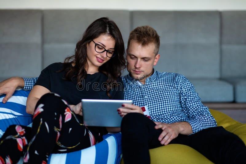 Romantiker kopplade av barnet kopplar ihop genom att använda minnestavladatoren på soffan arkivbild