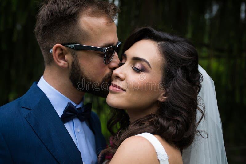 Romantiker kyssande härlig brud för sinnlig stilig brudgum på royaltyfri bild