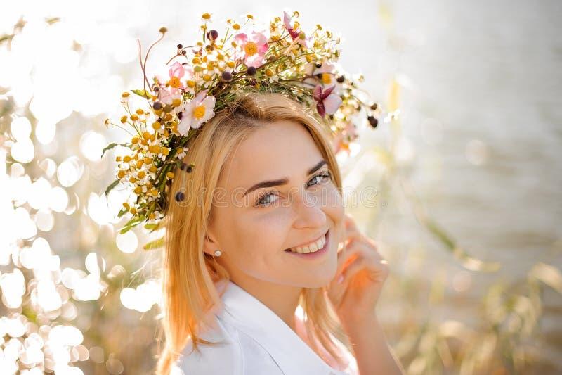 Romantiker som ler den blonda flickan i en krans av blommor royaltyfria bilder